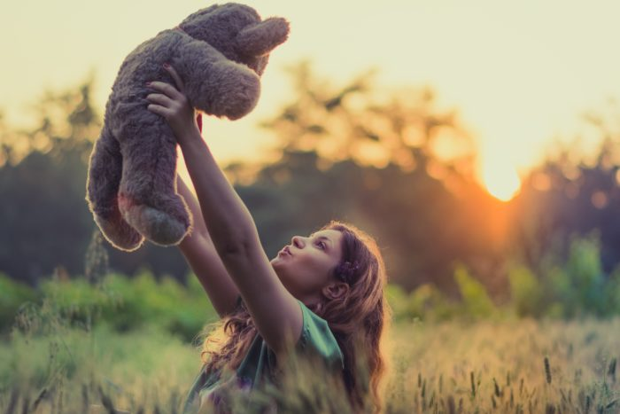 Woman holding a teddy bear up in a field.